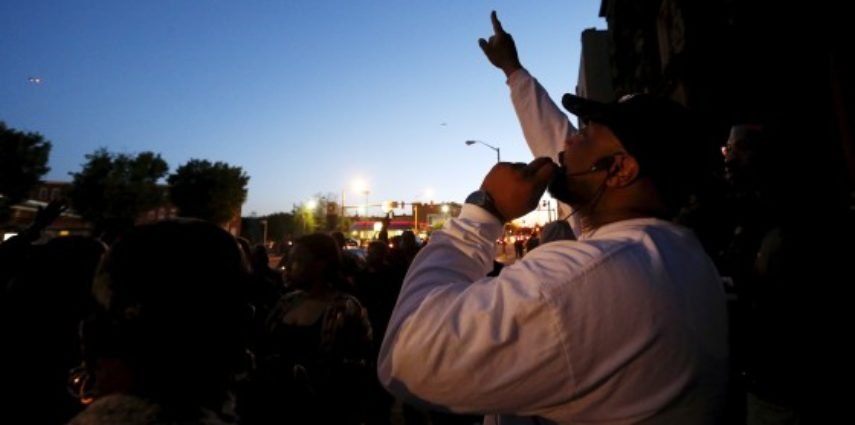 Pastor Gabriel Churn of West Baltimore's Union Temple Congregation leads his congregation in a prayer for peace in their neighborhood during a sunset prayer service on the sidewalk in front of their church near the scene of recent rioting over the death of 25-year-old Freddie Gray while in police custody in Baltimore, Maryland April 28, 2015.  REUTERS/Jim Bourg - RTX1AQKC