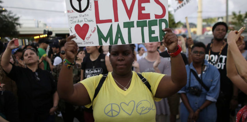 Desiree Griffiths, 31, of Miami, holds up a sign saying